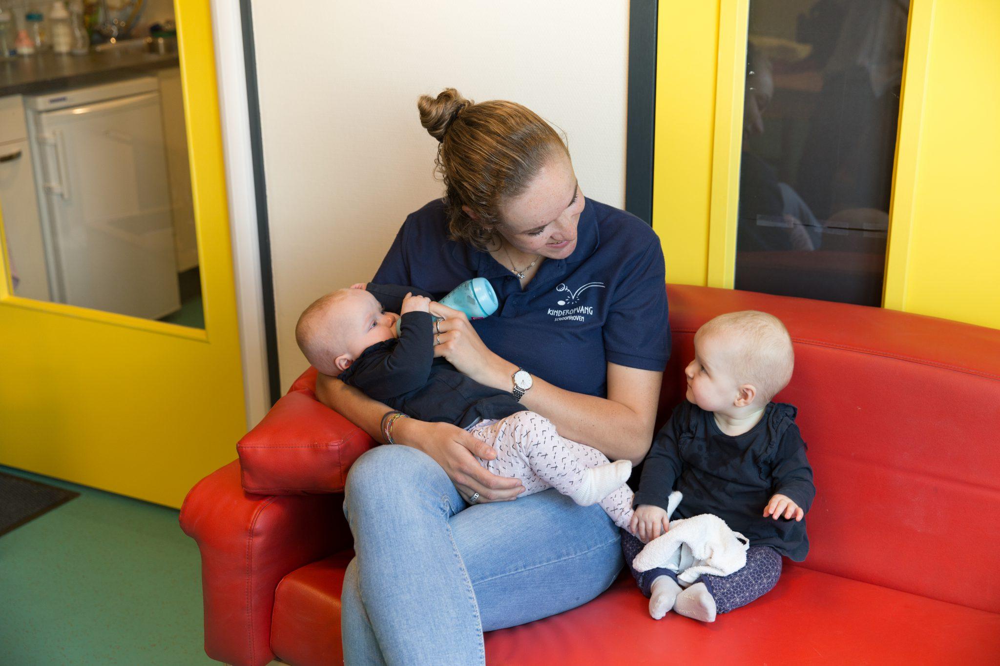 Pedagogisch medewerker geeft fles aan baby op de Kinderdagopvang (KDV)