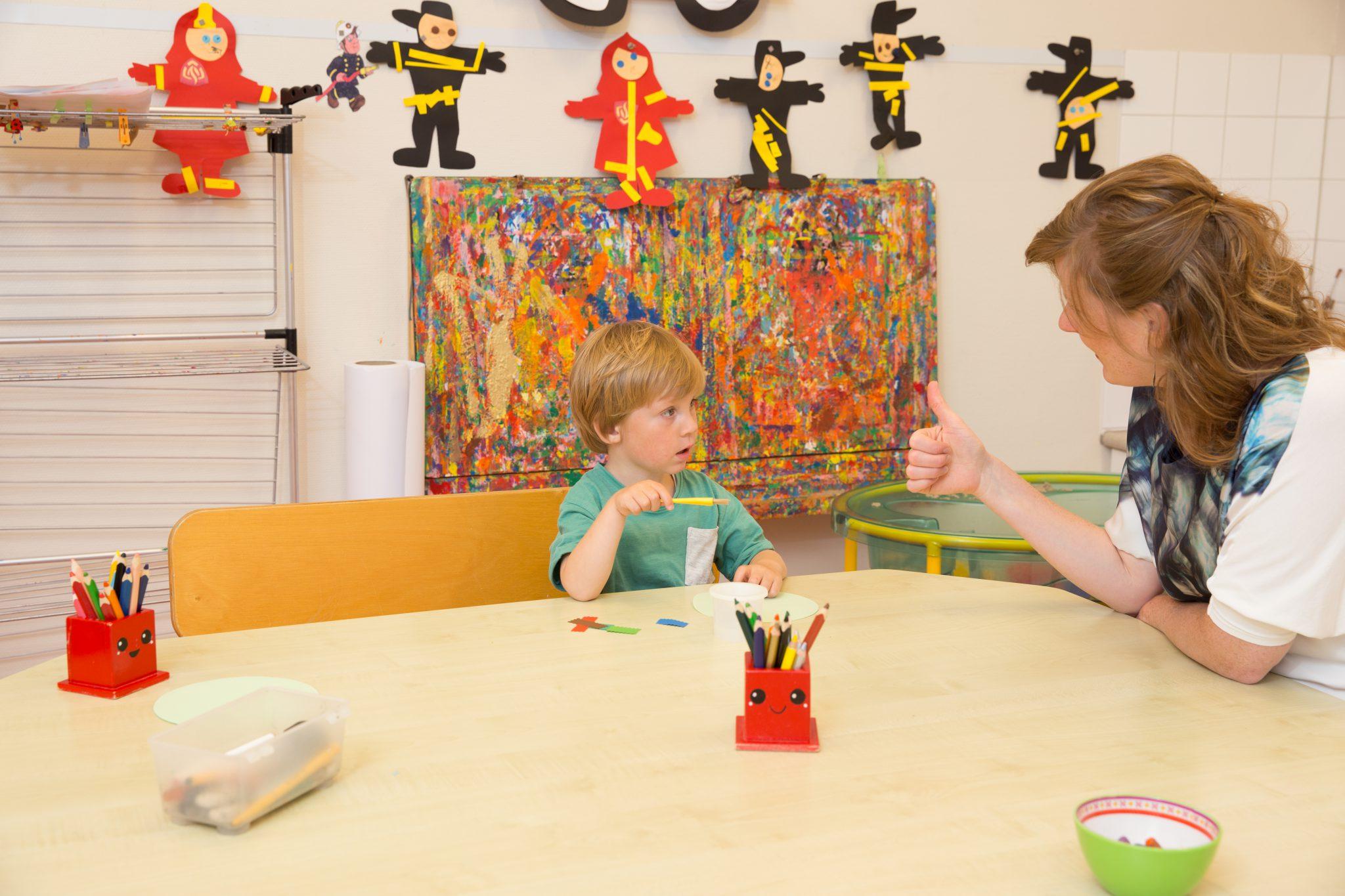 Kind en pedagogisch aan tafel. We streven ernaar onze tarieven zo laag mogelijk te houden.